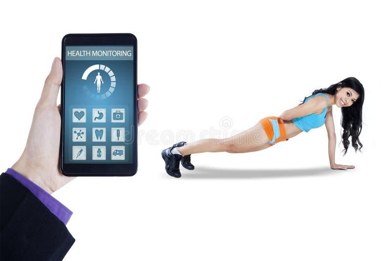 Woman doing push up with health app stock photos