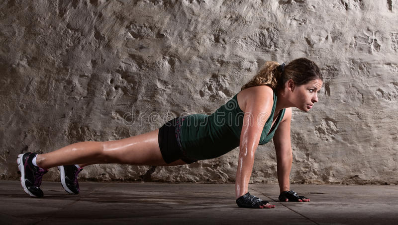 Woman Doing Push-ups Alone. Pretty young doing push ups and sweating royalty free stock image