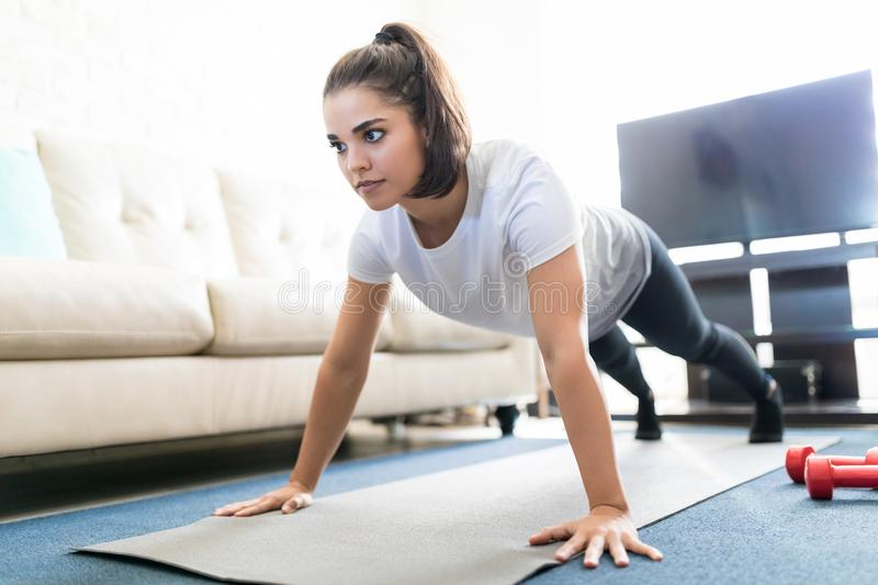 Woman doing push ups in living room. Healthy and strong young hispanic woman doing push ups on fitness mat in living room royalty free stock image