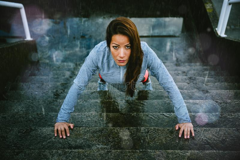 Woman doing push ups in stairs on winter rainy day. Motivated woman doing push ups in urban stairs under the rain during outdoor fitness workout. Healthy stock photo