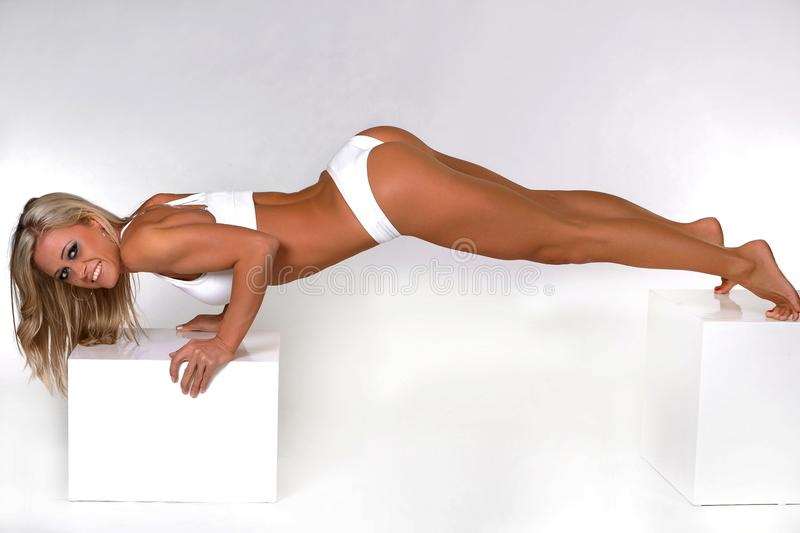 Woman doing push ups. A woman in white sports underwear doing push ups on two boxes stock image
