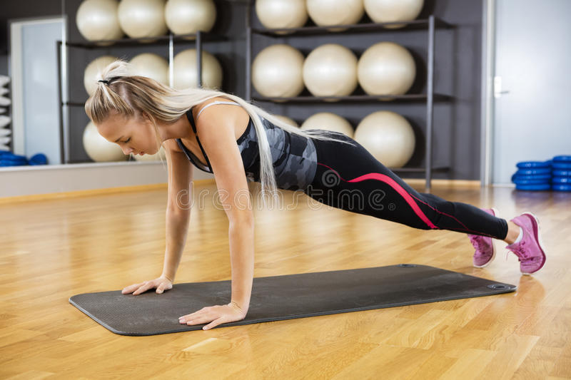 Woman Doing Pushups On Exercise Mat In Gym royalty free stock photography
