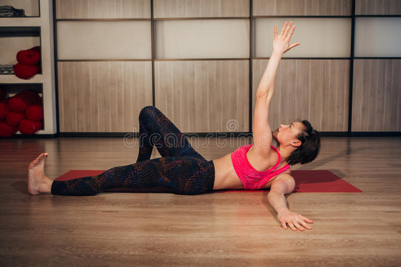 Woman doing Reclining Big Toe yoga pose, this stretches groins royalty free stock images
