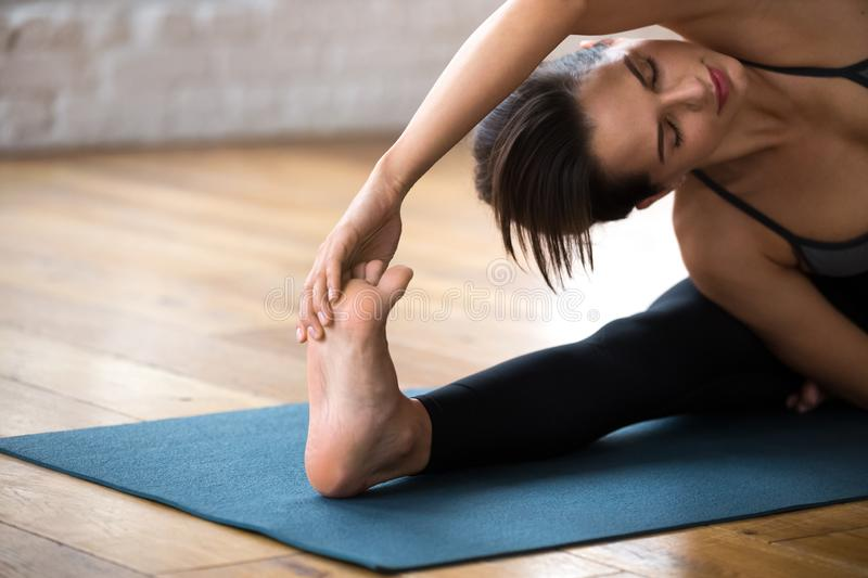Woman doing Revolved Head to Knee Forward exercise, close up. Young sporty attractive woman practicing yoga, doing Revolved Head to Knee Forward exercise royalty free stock photos