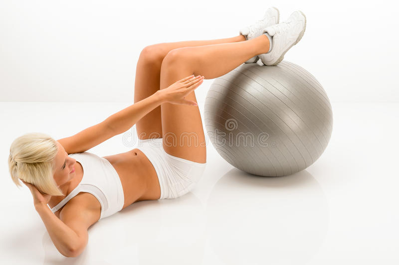 Woman doing sit-ups on fitness ball white royalty free stock photos