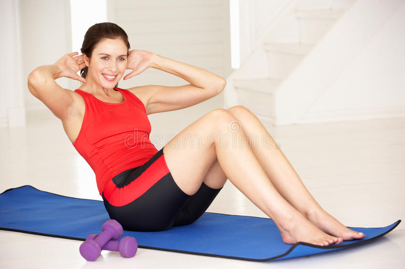 Woman doing sit-ups in home gym. Smiling off camera royalty free stock photo