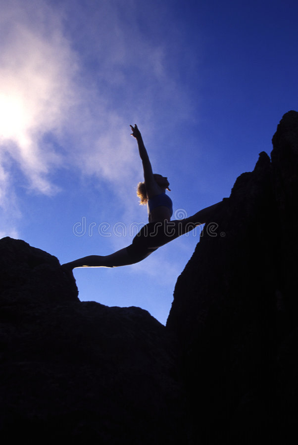 Woman doing splits on a mountaintop royalty free stock photo
