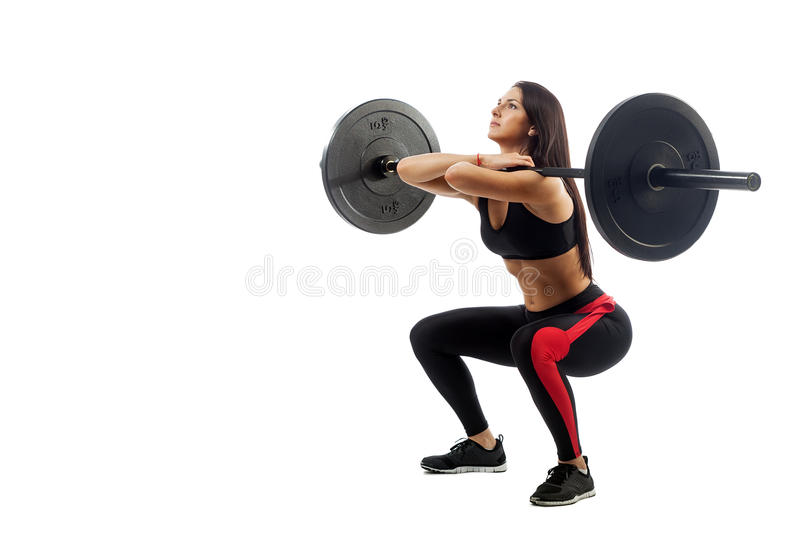 Woman doing squat with barbell. Young athletic brunette woman doing squat with a barbell, loki in front of him, position full sucker on white isolated background royalty free stock images