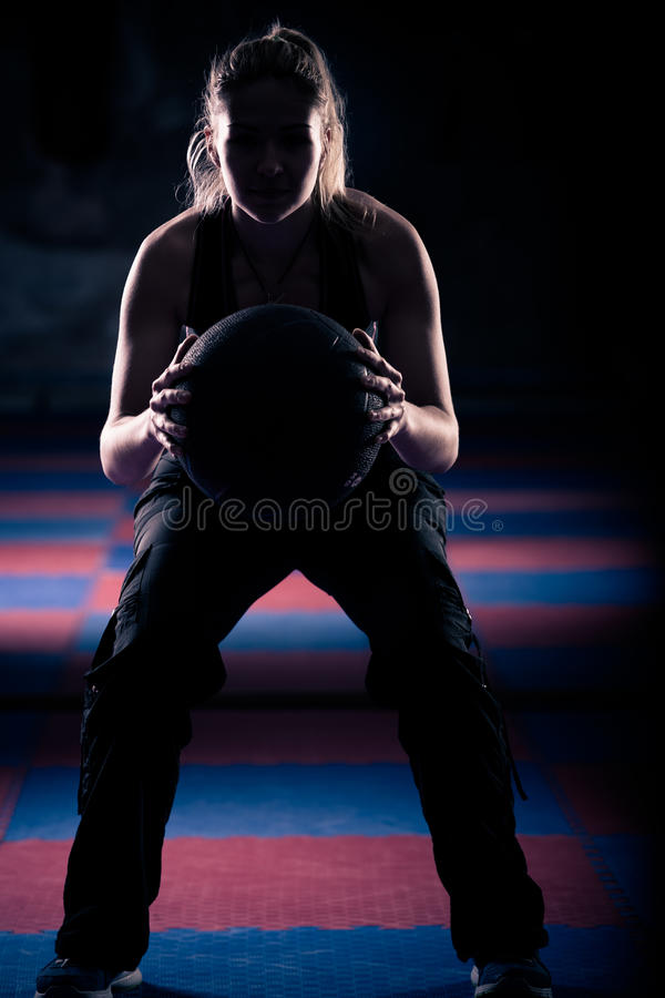 A woman doing a squat with her medicine ball. royalty free stock photography