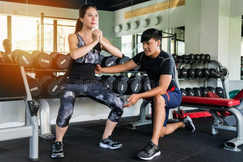 Woman doing squat with a personal trainer. Young asian fitness women doing squat exercise at the gym with a personal trainer stock photo