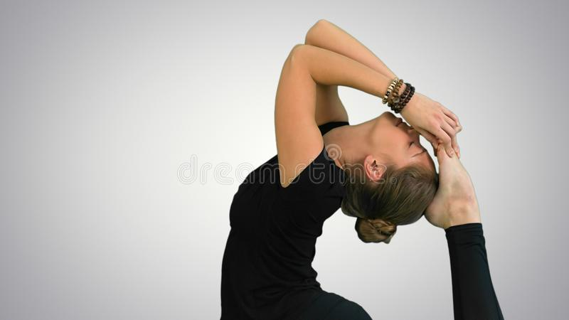 Woman doing stretching exercises, practicing yoga on white background stock photo