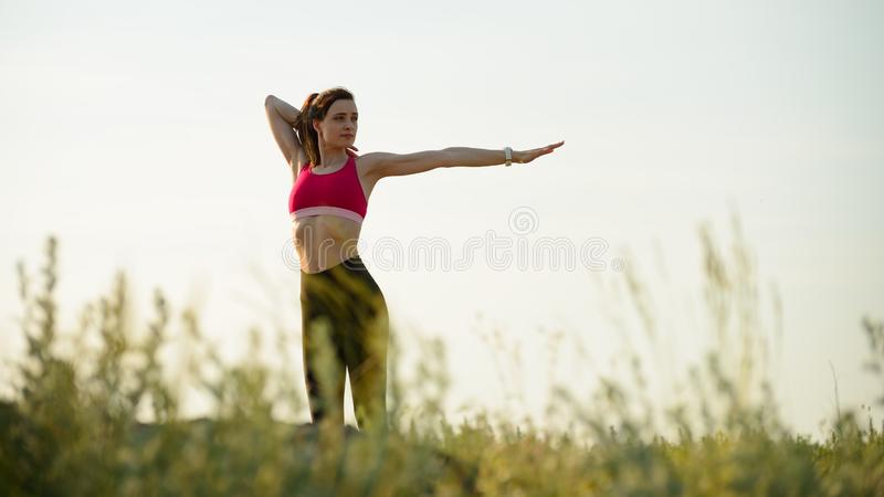 Woman Doing Stretching Outdoor. Warm up Exercise in the Summer Evening. Sport and Healthy Active Lifesyle Concept. Young Woman Doing Stretching Outdoor. Warm up royalty free stock photo
