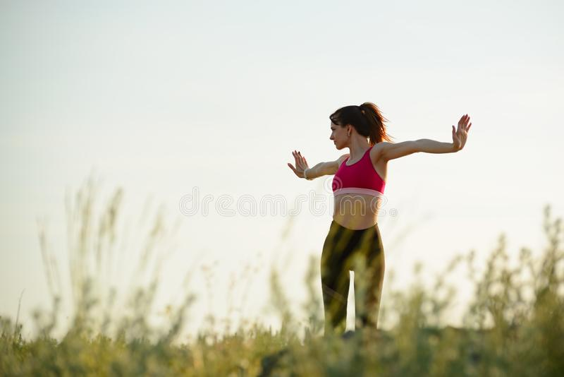 Woman Doing Stretching Outdoor. Warm up Exercise in the Summer Evening. Sport and Healthy Active Lifesyle Concept. Young Woman Doing Stretching Outdoor. Warm up stock photo