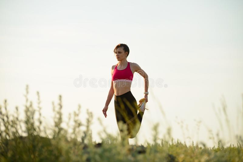 Woman Doing Stretching Outdoor. Warm up Exercise in the Summer Evening. Sport and Healthy Active Lifesyle Concept. Young Woman Doing Stretching Outdoor. Warm up stock image