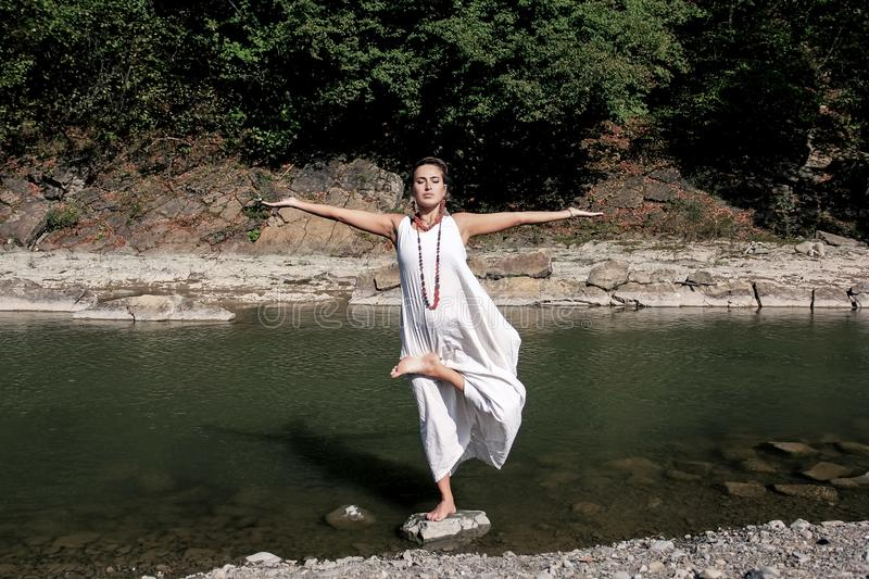 Barefoot girl standing in the water and doing yoga exercises, royalty free stock images