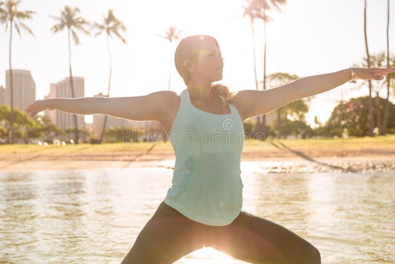Woman doing SUP yoga in Waikiki at sunrise warrior pose royalty free stock photography