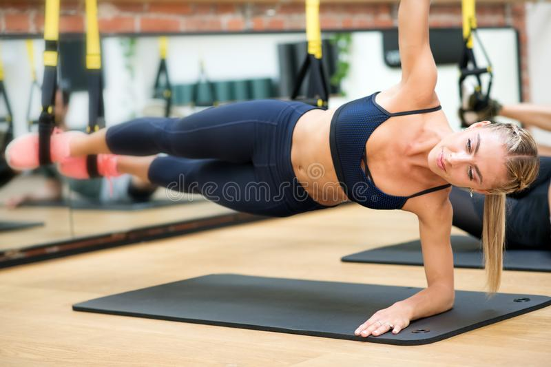 Woman doing suspended elbow side plank with trx stock image