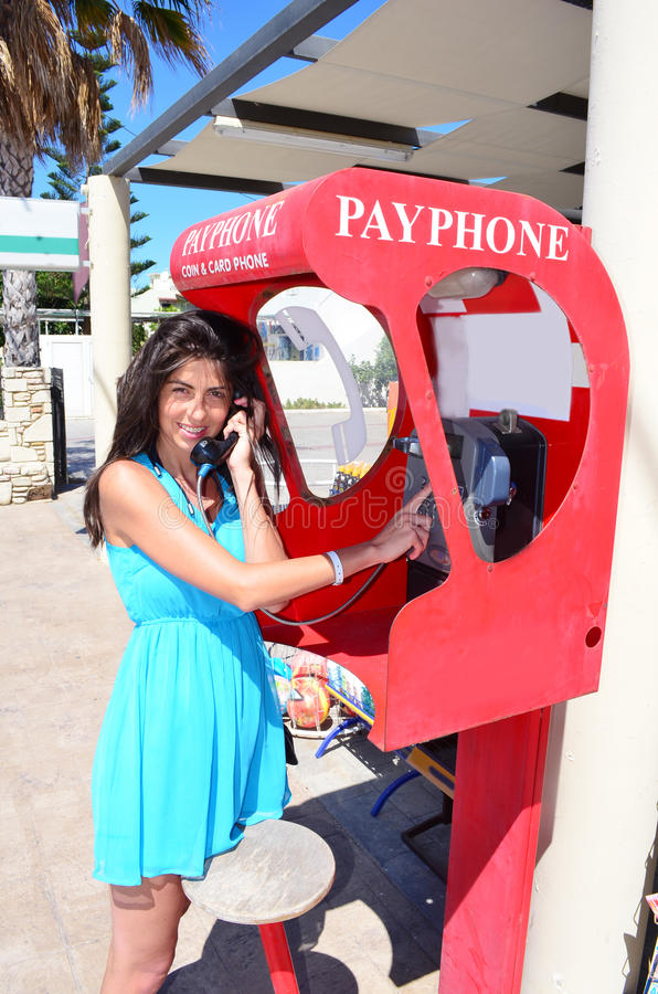A woman is doing a telephone call inside a telephone box. royalty free stock photo