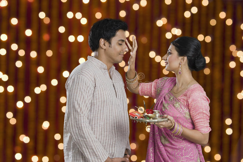 Woman doing tilak of her husband on Diwali stock photo