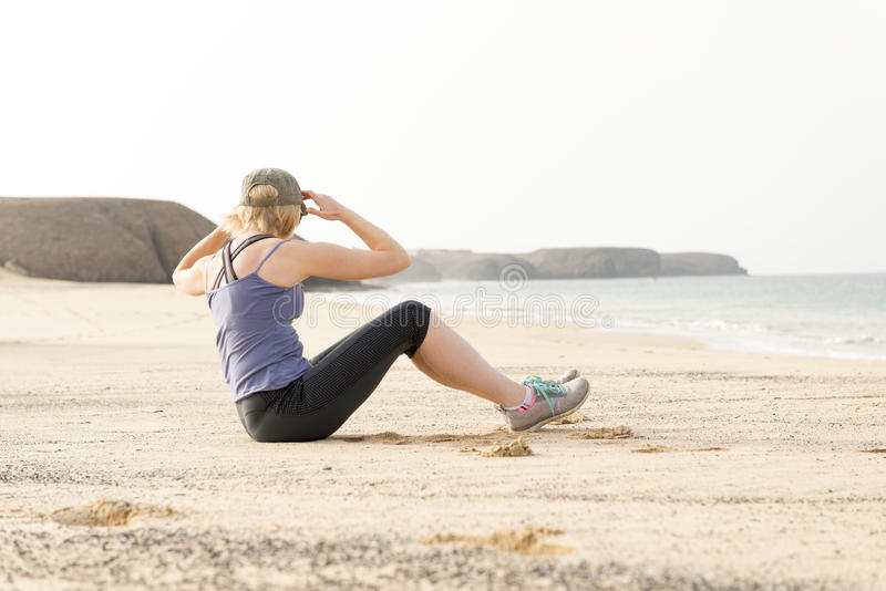 Woman Doing Torso Stretches by the Seaside stock photo