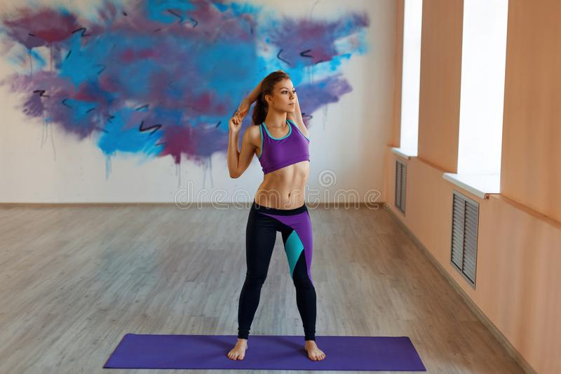 Woman doing warm-up on a background of graffiti. Woman young beautiful doing warm-up on a background of graffiti royalty free stock photos