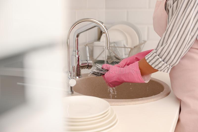 Woman doing washing up in kitchen sink, closeup view stock photography