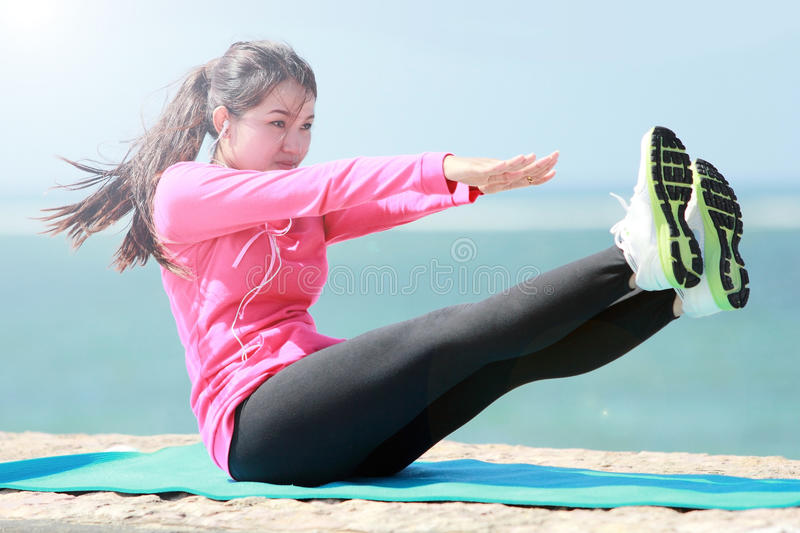 Woman doing workout in the beach stock image