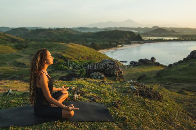 Woman doing yoga alone at sunrise with mountain view. Harmony with nature. Woman doing yoga alone at sunrise with mountain and ocean view. Harmony with nature royalty free stock image