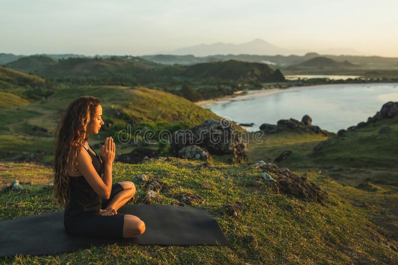 Woman doing yoga alone at sunrise with mountain view. Harmony with nature. Woman doing yoga alone at sunrise with mountain and ocean view. Harmony with nature royalty free stock photos