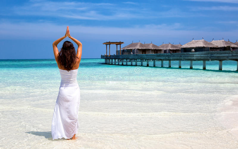 Woman doing yoga on a beach stock images