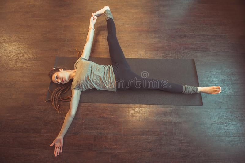 Woman doing yoga. Beautiful caucasian woman with long hair and slender body doing yoga on a mat top view royalty free stock images