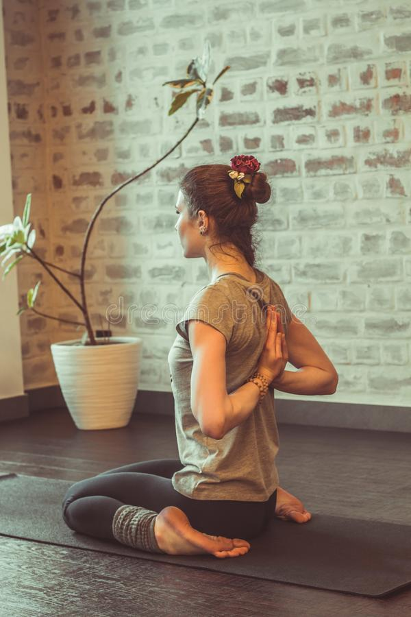 Woman doing yoga. Beautiful young woman practicing yoga indoor against brick wall in studio, dark toned stock photo