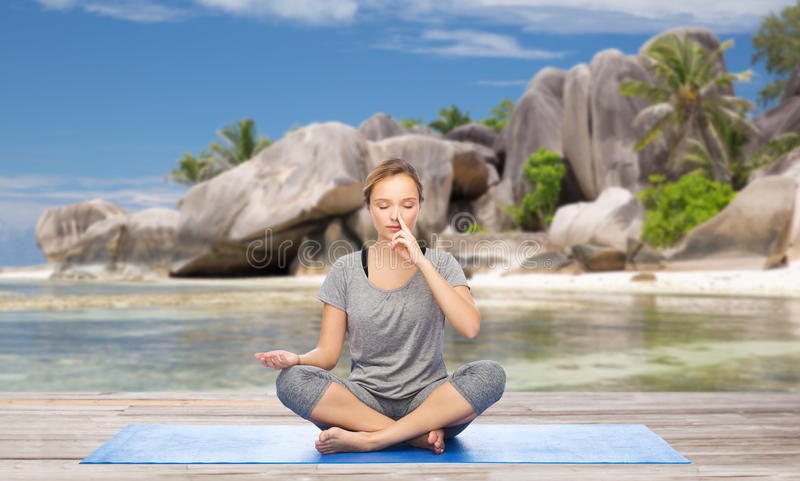 Woman doing yoga breathing exercise on beach stock photography