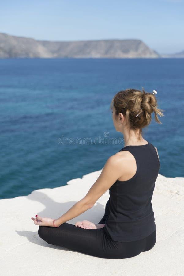 Woman doing yoga. Brown hair woman doing yoga on top of a mountain royalty free stock photo