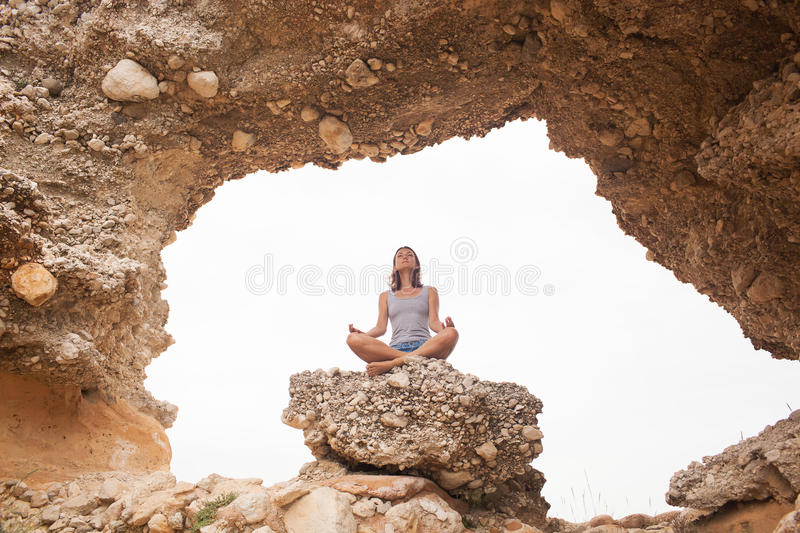 Woman doing yoga. On the cave background stock photos