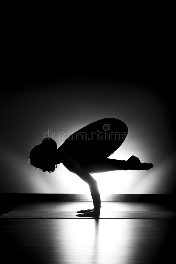 Woman doing yoga crow pose silhouette black and white stock photo