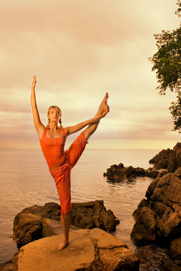 Woman doing yoga exercise. Beautiful young woman doing yoga exercise outdoors stock image