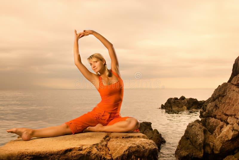 Woman doing yoga exercise. Beautiful young woman doing yoga exercise outdoors stock photography