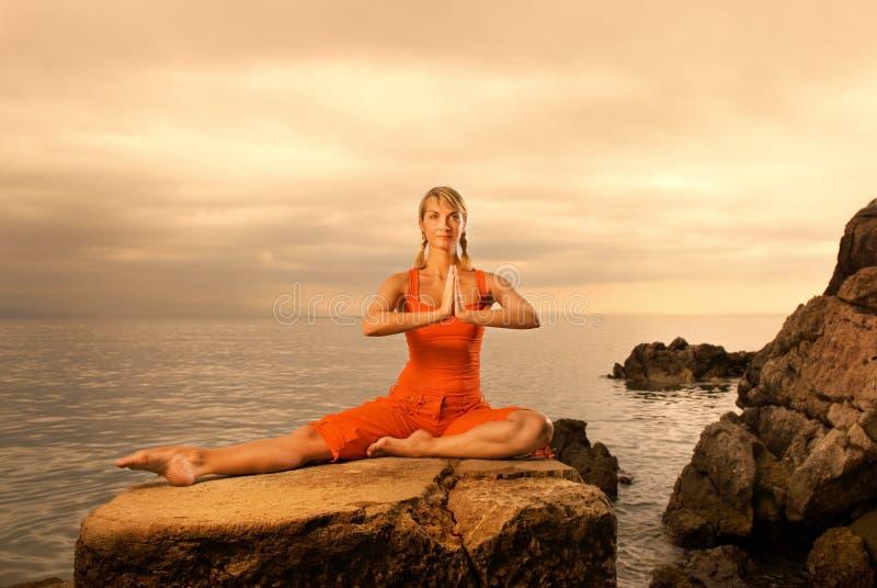 Woman doing yoga exercise. Beautiful young woman doing yoga exercise outdoors stock photo
