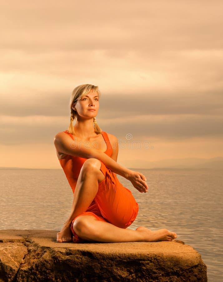 Woman doing yoga exercise. Beautiful young woman doing yoga exercise outdoors stock photos