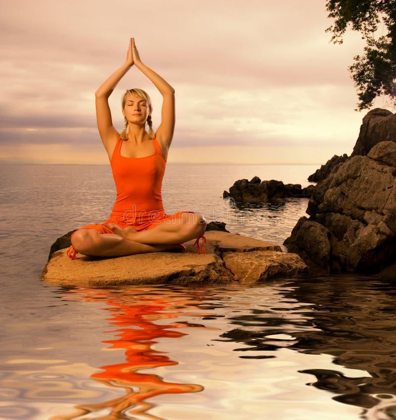 Woman doing yoga exercise. Beautiful young woman doing yoga exercise outdoors royalty free stock photos