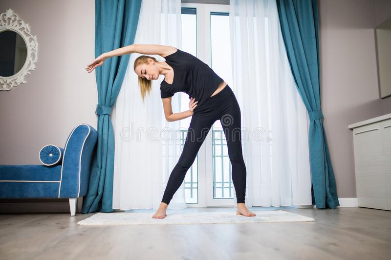 Woman doing yoga exercise at home. Morning workout in bedroom. Healthy and sport lifestyle. Woman doing yoga exercise on bed at home. Morning workout in bedroom stock photo