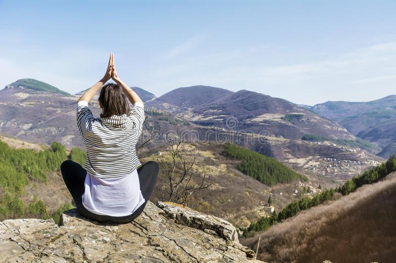 Woman Doing Yoga Exercise Outdoor. Young girl doing yoga fitness exercise outdoor on a beautiful mountains landscape royalty free stock photo