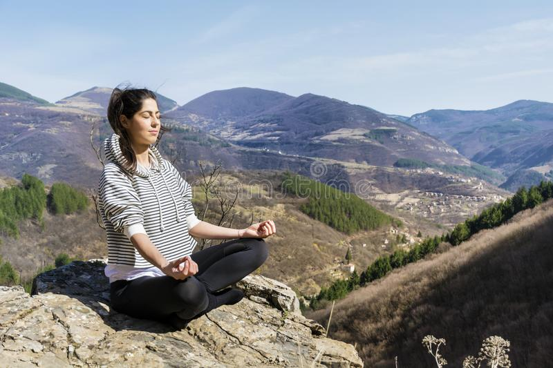 Woman Doing Yoga Exercise Outdoor. Young girl doing yoga fitness exercise outdoor on a beautiful mountains landscape royalty free stock image