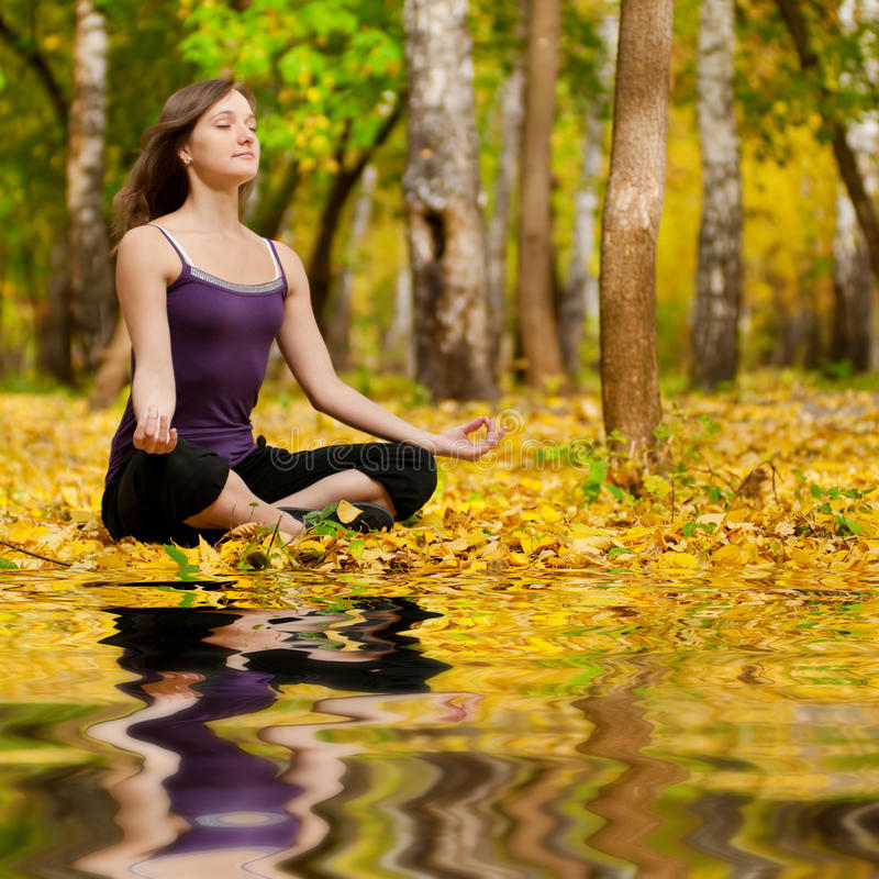 Woman doing yoga exercises in the autumn park stock images