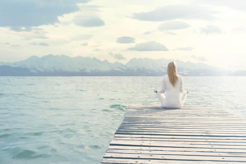 Woman doing yoga exercises in front of a spectacular scenery. Woman doing yoga exercises in front of a spectacular view royalty free stock image
