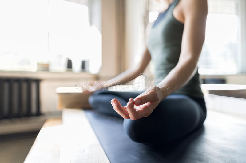 Woman Doing Yoga Exercises In Gym, Closeup Sport Fitness Girl Sitting Lotus Pose. Meditation Relaxation stock photo