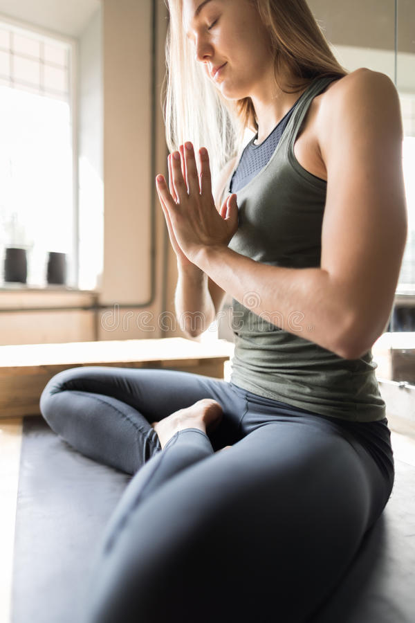 Woman Doing Yoga Exercises In Gym, Sport Fitness Girl Sitting Lotus Pose. Meditation Relaxation royalty free stock image