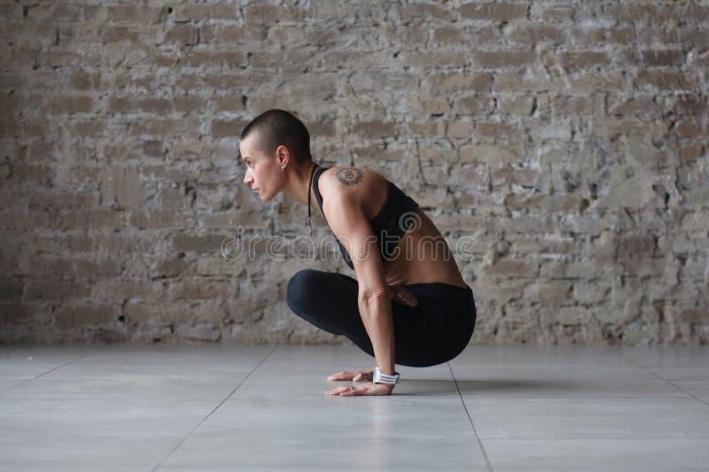 Woman doing yoga indoor. Young skinhead woman doing yoga balance exercise - tolasana indoor stock photography