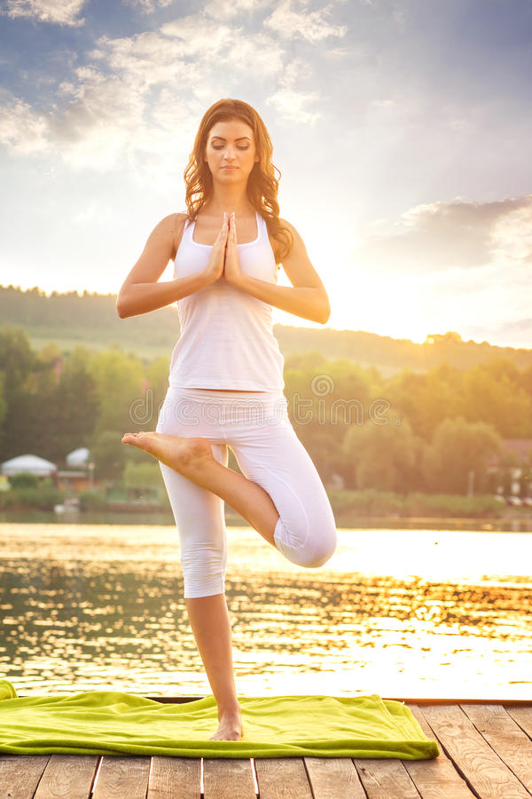 Woman doing yoga on the lake - beautiful lights royalty free stock photos